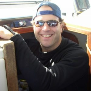 Fourth Element Xerotherm Baselayer Top worn by a man on a boat with a hat and glasses