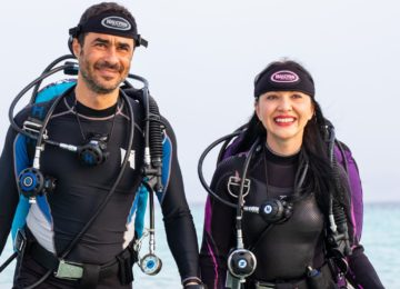 Scuba Regulators and Equipment worn by a male and a female walking out of the water onto a beach holding hands and smiling with there mask straps on facing logo towards the camera and the masks behind their heads