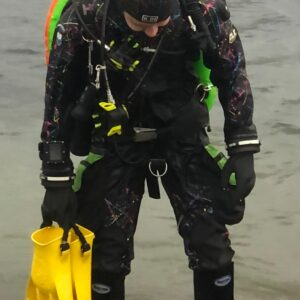 dui clx450 multicolour drysuit worn by dive shop staff member Ross wearing it with yellow jet fins, kubi dry glove cuffs, orange, yellow and green double tank with with a pair of double faber 100 cubic foot tanks